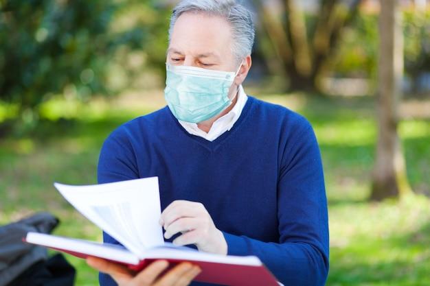 Мужчина читает книгу в парке в маске