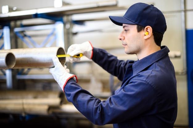 パイプのサイズを測定する産業プラントの労働者