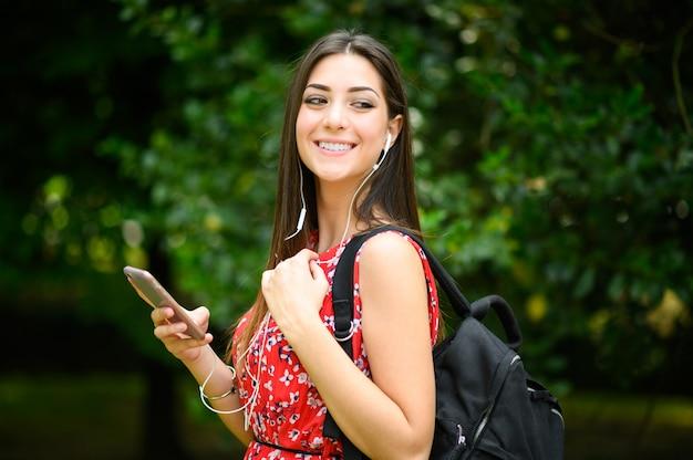 Студентка гуляет в парке, используя свой смартфон для прослушивания музыки