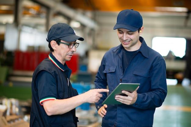 Рабочие с помощью планшета на современном заводе