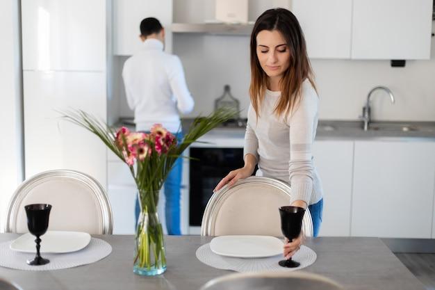 彼女のボーイフレンドが料理している間にテーブルを設定する女性