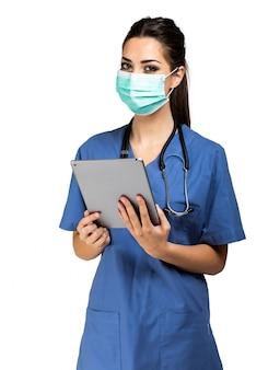 デジタルタブレットを使用して、白で隔離されるマスクを身に着けている看護師