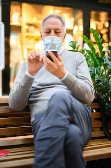 Старший мужчина сидит на скамейке и с помощью смартфона в торговом центре носить маску