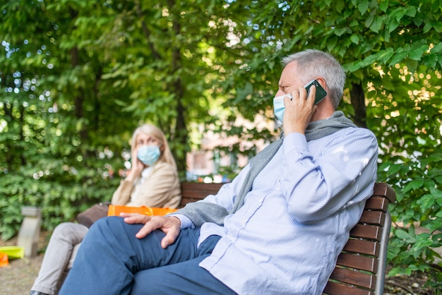 公園のベンチ、コロナウイルスの安全性、社会的距離概念の女性との距離を保ちながら電話で話している男性