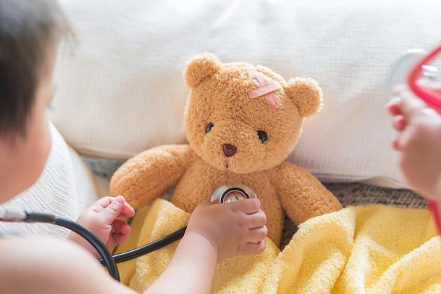 Симпатичная девочка играет врач со стетоскопом и плюшевым мишкой.