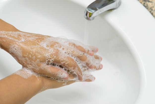 水で蛇口の下で石鹸で手を洗う女性