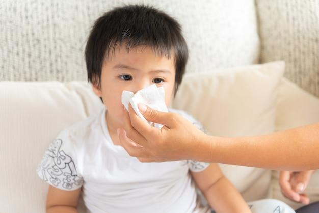 母親の助けを求める娘が居間で鼻を吹く