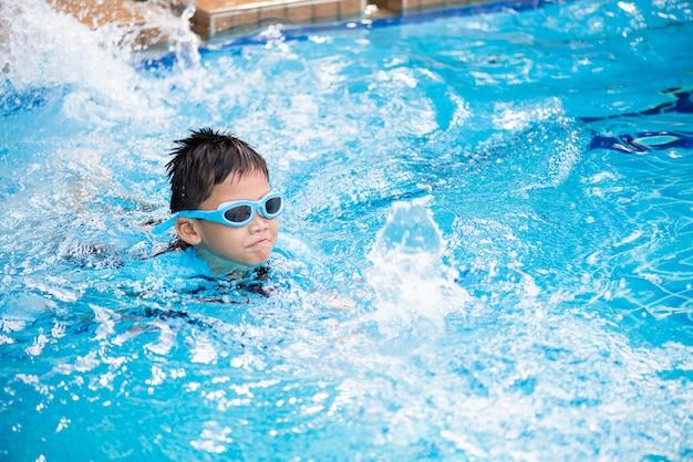 Мягкий фокус на счастливый молодой азиатский ребенок с плавать очки, плавающие в бассейне
