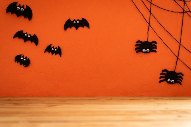 ハロウィーン工芸品、バット、クモ、オレンジの背景にクモの巣。