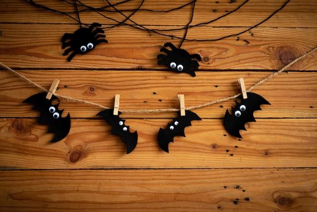 ハロウィーンの工芸品、コウモリ、クモ、木製のテーブルの背景にクモの巣