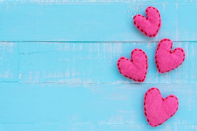 青と白の色の木製の背景に手作りピンクの心のトップビュー