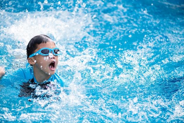 Счастливый азиатский ребенок с плавать очки, купание в бассейне.
