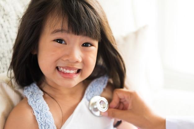 Доктор осматривает маленькую девочку, используя стетоскоп. концепция медицины и здравоохранения.