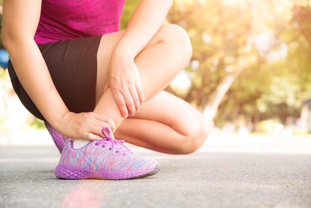 Женщина, страдающая от травмы лодыжки во время тренировки.