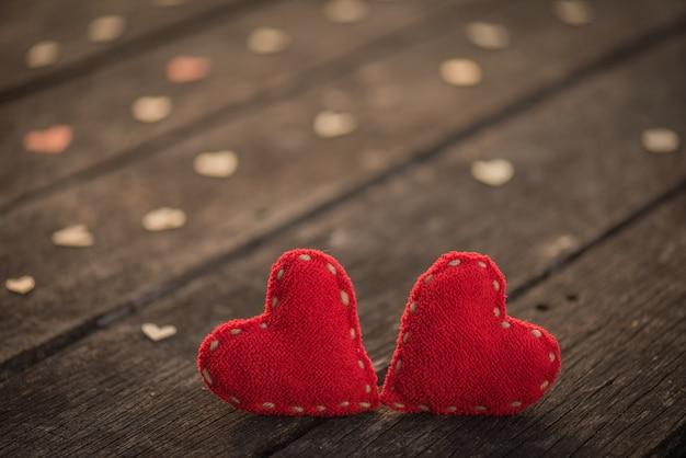 Два красных сердца с большим количеством деревянных сердец на деревянном фоне