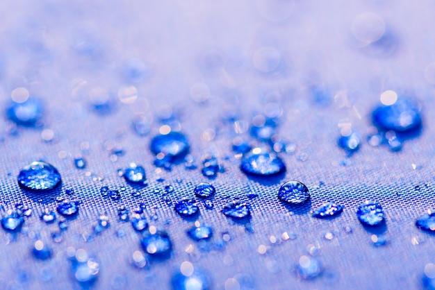 青い防水布の背景の上に水滴のパターンを閉じます