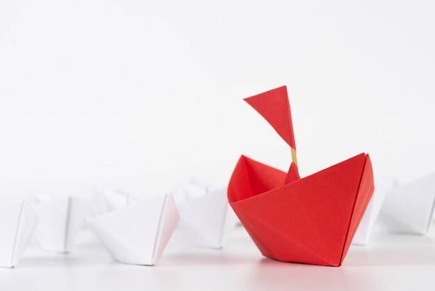 リーダーシップの概念。白の中で赤い紙の船のリード。