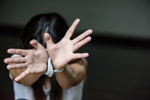 Женская рука была привязана веревкой. остановить насилие