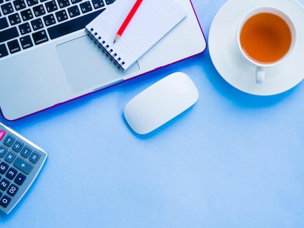 青い背景にオフィスアクセサリーとトップビュー女性の机のワークスペース。