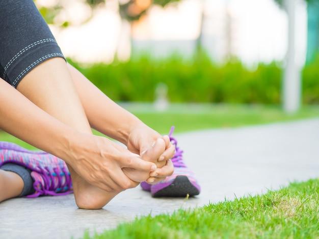 彼女の痛みを伴う足をマッサージする女性。