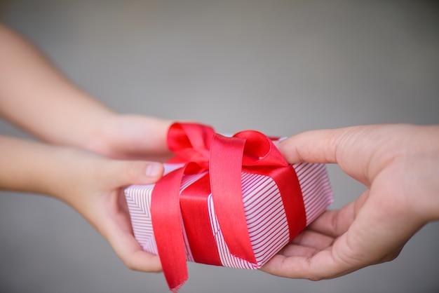 彼女の子供にギフトボックスを与える母の手。休日、プレゼント、クリスマス