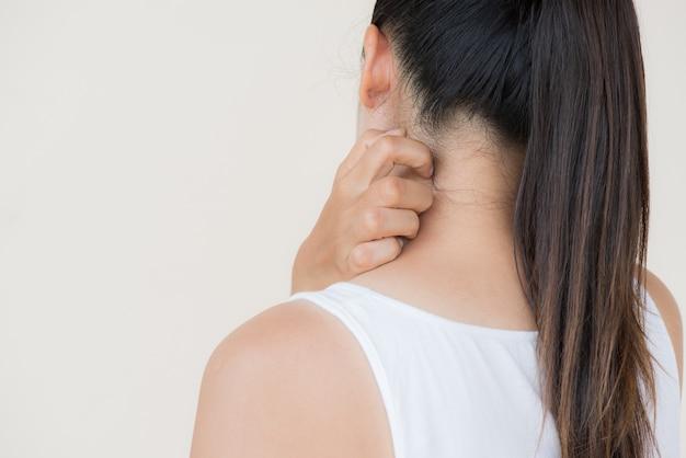 女性の手は、首と背中で手でかゆみを引っかく。ヘルスケアと医療のコンセプト。
