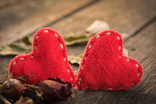 Сушеная красная роза, мертвая красная роза с двумя красными сердцами на деревянном фоне