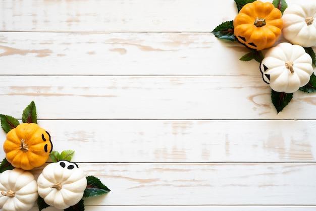 Вид сверху белых и желтых тыкв призраков на деревянном фоне. концепция хэллоуина.