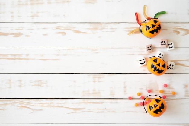 Вид сверху желтые призрачные тыквы с желе червяком на деревянном фоне. концепция хэллоуина.
