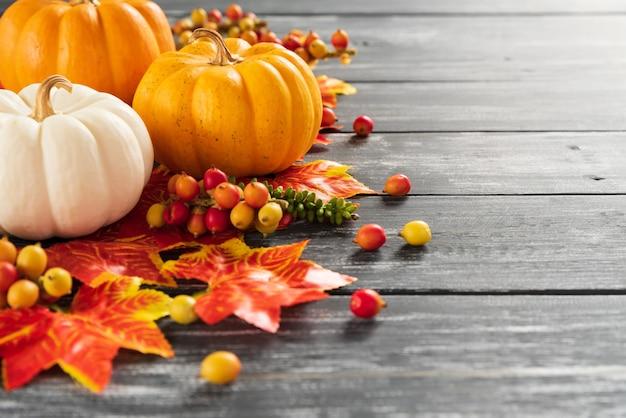 秋のカエデの葉と古い木製の背景にカボチャ。感謝祭の日のコンセプト。