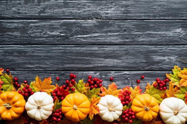 秋のカエデはカボチャと古い木製の背景に赤い果実と葉。