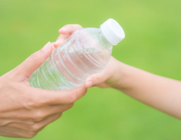 緑色の草の背景に子供に新鮮な水のボトルを与えるクローズアップの女性の手。