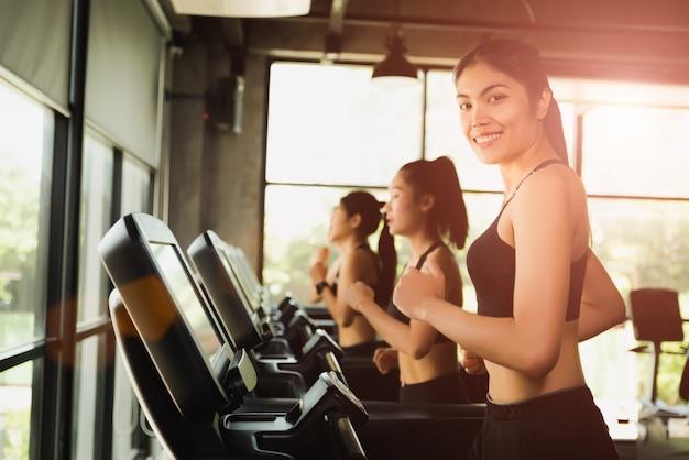 現代スポーツジムのトレッドミルで走ったり、ジョギングしたりする女性。運動とスポーツのコンセプト。