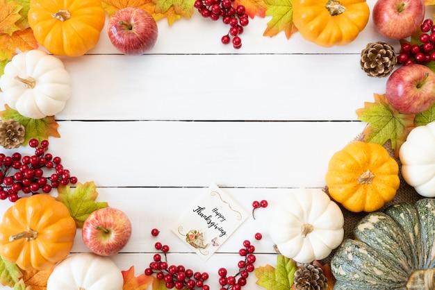 木製の背景にカボチャと赤い果実と秋の葉が残っています。