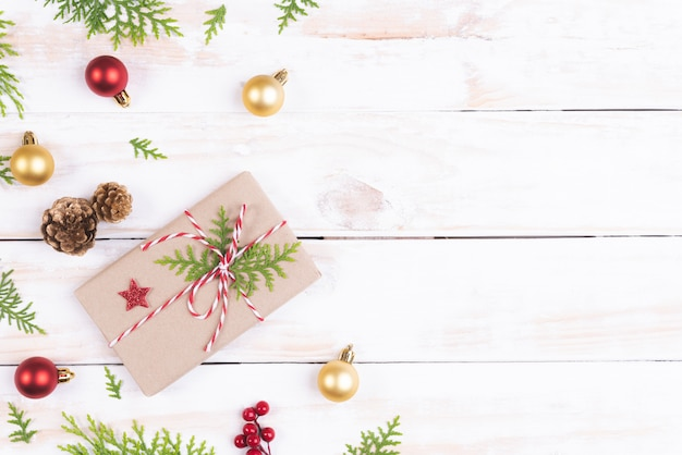 クリスマスツリーの上にスプルースの枝、松のコーン、赤い果実とギフトボックスのトップビュー