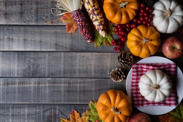 木製の背景にカボチャと赤い果実と秋の葉が残っています。感謝祭のコンセプト