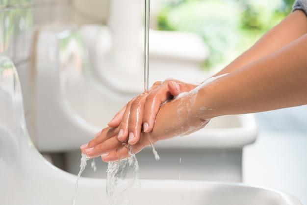 蛇口の下で石鹸で手を洗うクローズアップ女性。