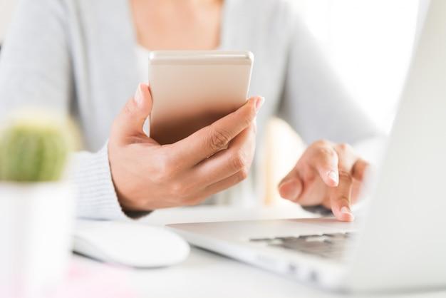 オフィスでラップトップとテーブルの上に白い携帯電話を持っている女性の手