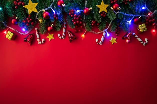 赤い背景にクリスマススプルースの枝、松のコーン、赤い果実とベルのトップビュー。