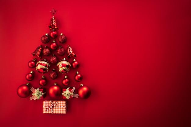 赤い背景にクリスマスツリーの形の赤いボールと鐘とギフトボックスのトップビュー。