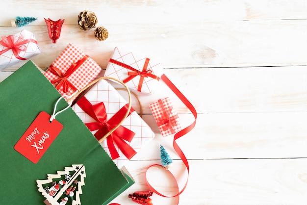 Рождественская подарочная коробка и зеленая хозяйственная сумка с тегом сообщения