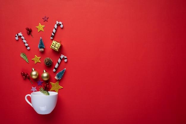 Белая чашка всплеск рождественские украшения на красном фоне.