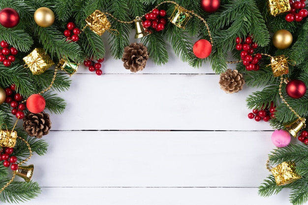 クリスマスのギフトボックス赤いボールのトウヒの枝、松のコーン、赤い果実の木製の背中