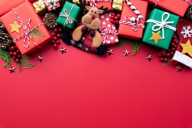 赤い背景にトナカイと装飾とクリスマスのギフトボックス。