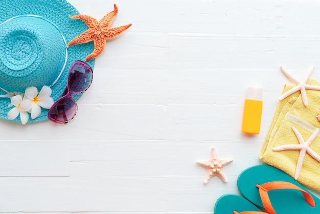 夏の休日のための明るい青色のパステルの木製の背景にビーチアクセサリー