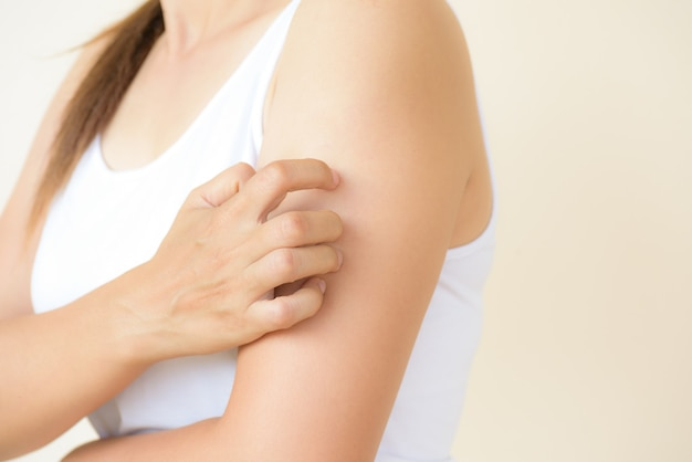 女性の腕は自宅で手でかゆみを傷つける。ヘルスケアと医療のコンセプト。