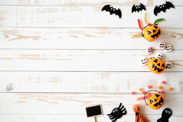 Желтые призрачные тыквы с желе червяком на белом деревянном фоне. концепция хэллоуина.