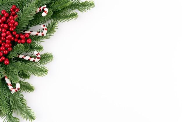 Рождественские фон еловые ветки и красные ягоды на белом фоне.