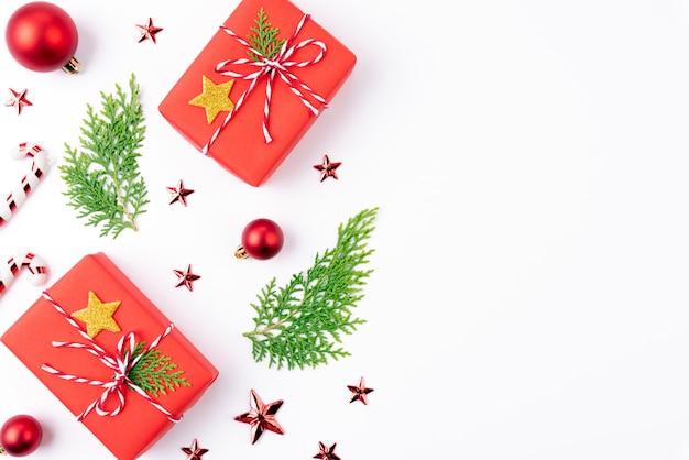 Рождественский фон подарок с еловыми ветками, красная звезда на белом фоне.
