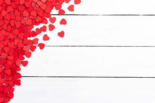 バレンタインデーの背景、白い背景に小さな木製の赤い心。